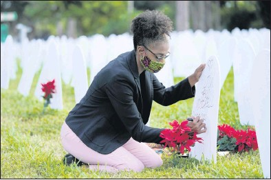 """?? THE ASSOCIATED PRESS ?? On Tuesday, RachelMoore wrote a tribute to her cousin, Wilton """"Bud"""" Mitchell, who died of COVID-19. Shewas at a symbolic cemetery in the Liberty City neighborhood of Miami thatwas created to remember and honor lives lost to the disease."""