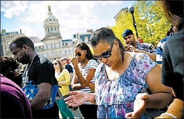 ?? DAVID GOLDMAN/AP ?? Maryland resident Kim Thomas prays Sunday in front of Baltimore's City Hall, where hundreds of jubilant people gathered for a rally. A 10 p.m. to 5 a.m curfew that had been in place on the city since Tuesday was lifted on the same day.