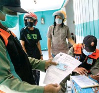 ?? ALFIAN RIZAL/JAWA POS ?? TINDAKAN TEGAS: Pengendara sepeda motor yang tidak mengenakan masker terjaring petugas gabungan satpol PP dan polisi di Jalan Jetis Kulon kemarin. Tim operasi yustisi berhasil menyita 27 KTP dari para pelanggar.