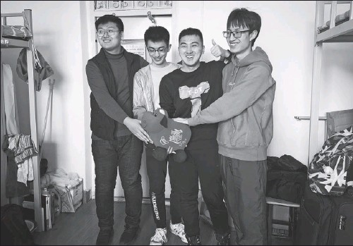 ?? PHOTO BY WANG YING / XINHUA ?? Cao Pengjun (second right), a junior at Northeastern University in Shenyang, Liaoning province, celebrates Lunar New Year with three temporary roommates in the dormitory.