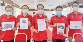 ??  ?? Lui (centre) and KKCCCI committee members holding up documents and pictures that showcased the chamber's transparency in carrying out the process of land swap as voted by majority of the members attending the EGM held in July 2020.