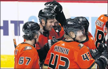 ?? DAVID ZALUBOWSKI — THE ASSOCIATED PRESS ?? The Ducks' Ryan Getzlaf, back left, is congratulated on his overtime goal during Saturday's comeback win in Colorado.