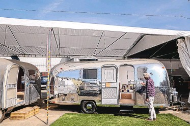 ?? SANDY HUFFAKER/THE WASHINGTON POST ?? Denny Stone, owner and head of design at So Cal Vintage Trailer, polishes a refurbished Airsteam at his facility in San Diego.