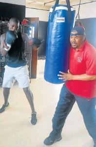 ?? PHOTOGRAPH: YONELA MOFU ?? WORKING HARD: Coach Caiphus Ntante working with boxer Sinethemba Gungqisa