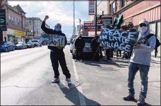 ?? Tyler LaRiviere / Associated Press ?? Enrique Enriquez, left, and a community activist rally on 26th St. after the body camera footage of Chicago police killing Adam Toledo was released on Thursday.