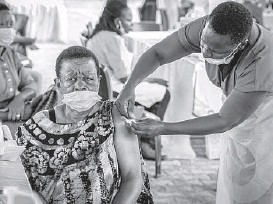 ?? NICHOLAS BAMULANZEKI/AP ?? A woman receives a coronavirus vaccination in Kampala, Uganda. While Africa's 1.3 billion people account for 18% of the world's population, the continent has received just 2% of all vaccine doses administered globally.