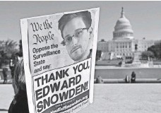 ?? MAN­DEL NGAN, AFP/GETTY IMAGES ?? A protester in Washington in 2013 on be­half of NSA whistle­blower Ed­ward Snow­den, who wants to re­turn from Moscow.