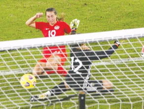 ?? GREGG NEWTON / AFP VIA GETTY IMAGES ?? Canada's Sarah Stratigakis nudges the ball past goalkeeper Solana Pereyra of Argentina for the game's only goal at the Shebelieves Cup tournament in Orlando, Fla., on Sunday.