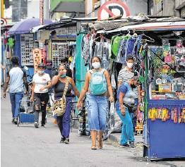 ??  ?? Dos mujeres caminan sobre la carrera 4 entre calles 13 y 14, en el centro de Cali. Los trabajadores informales fueron uno de los más afectados en la pandemia.