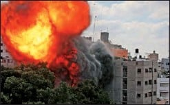 ??  ?? A ball of fire engulfs the Al-Walid building that was destroyed in an Israeli strike on Gaza on Thursday;