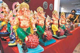 ?? R. RAGU ■ ?? Destroyer of evil: Pandemic-themed Ganesha idols kept for sale at the Poompuhar showroom in Chennai on the eve of Vinayaka Chaturthi festival on Friday.