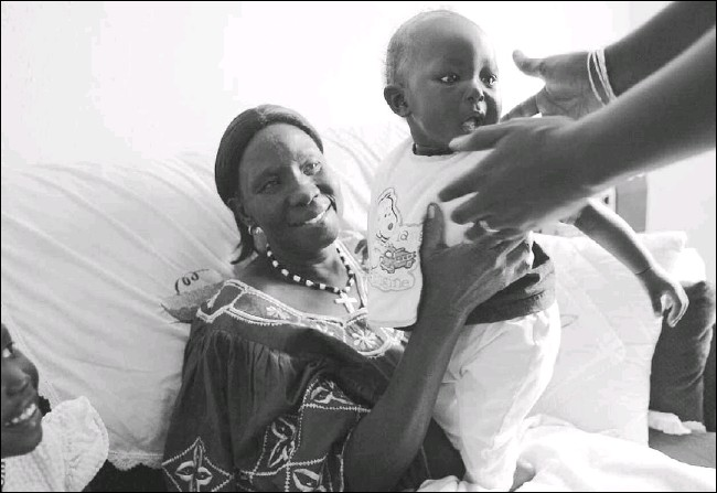 ?? Photos by SONYA HEBERT/Staff Photographer ?? Mary Pediet, a Sudanese refugee, hands 4-month-old Ajak Atem to his mother as sister Aguer Atem watches. Ms. Pediet escaped the refugee camps in Kenya, but her daughter remains there.