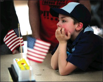 ??  ?? ABOVE: Justin Cournoyer, 6, watches as his car finishes in one of the Pinewood Derby heats on Saturday.