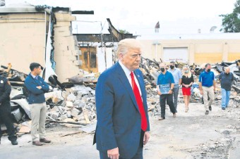 ??  ?? El presidente de Estados Unidos, Donald Trump, camina entre las ruinas de uno de los edificios incendiados por los grupos extremistas, en Kenosha, una de las ciudades víctimas de los ataques.