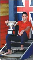 ?? REUTERS ?? Novak Djokovic poses with the Australian Open trophy — the 33-year-old's 18th Grand Slam title — at Melbourne's Brighton Beach on Monday.