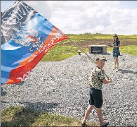 ?? Mstyslav Chernov Associated Press ?? A BOY WAVES a f lag of the self- proclaimed Donetsk People's Republic at a memorial to the victims of the downed Malaysian jetliner near the village of Hrabove.