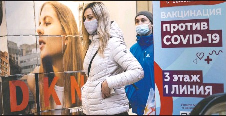 """??  ?? A woman wearing a face mask to protect against coronavirus walks past a poster reading """"vaccination against covid-19"""" at the GUM, the State Department store, near Red Square in Moscow. (AP/Alexander Zemlianichenko)"""