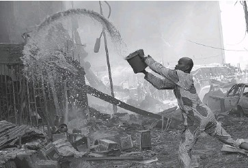 ?? SUNDAY ALAMBA/THE ASSOCIATED PRESS ?? A man tries to contain a fire at a warehouse full of fireworks on Lagos Island in Lagos, Nigeria, on Wednesday. The blaze threatened the densely populated surrounding city blocks, photo below. There was no word on possible casualties.