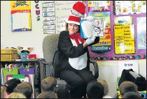 ?? CHRIS RILEY — TIMES-HERALD ?? Dressed as The Cat in the Hat, principal Wendy Smith celebrates Dr. Seuss' birthday on Wednesday by reading 'The Cat in the Hat' to a group of kindergart­ners at Mary Farmar Elementary in Benicia.