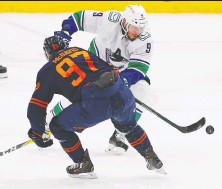 ?? PERRY NELSON-USA TODAY SPORTS ?? The Canucks' J.T. Miller chips the puck past the Oilers' Connor McDavid Saturday at Rogers Place in Edmonton.