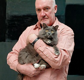 "??  ?? Scully cradles his pet cat. At 61, the painter feels ready to have a baby with Tomasko. He says the couple have the ""perfect environmen­t"" in which to raise a child"