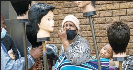 ?? Photo: AP ?? A woman carrying a child on her back looks at wigs on sale at the Baragwanath Taxi Rank in Soweto, South Africa, Wednesday, September 16.