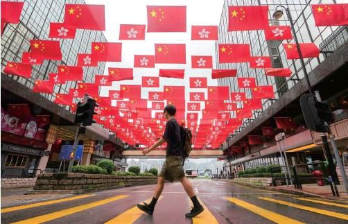 """??  ?? 6月29日,在香港尖沙咀一条街上,中华人民共和国国旗和香港特别行政区区旗一起迎风飘扬。""""七一""""临近,香港街头出现许多""""贺建党百年""""""""庆香港回归""""的喜庆元素。 东方IC图"""