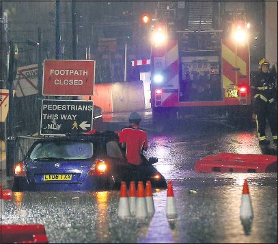 ?? Pictures: WEIR/VANTAGE NEWS, PETER MACDIARMID/LNP ?? Chaos on the A20 in Lewisham, London, with motorists stranded and fire crews battling floods yesterday