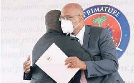 ?? VALERIE BAERISWYL/GETTY-AFP ?? Interim Prime Minister Claude Joseph, left, hugs designated Prime Minister Ariel Henry during a ceremony Tuesday at La Primature in Port-au-Prince, Haiti. Henry was sworn in to replace Joseph, who had assumed leadership of Haiti.