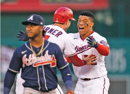 ?? AP PHOTO/ALEX BRANDON ?? Washington Nationals' Juan Soto, right, and Trea Turner celebrate in front of Atlanta Braves second baseman Ozzie Albies after Soto hit a game-winning single in the ninth inning Tuesday in Washington. Victor Robles scored on the play, and Washington won 6-5.