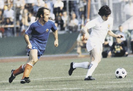?? Pictures: Johnston Press/sns ?? Main picture: Peter Lorimer plays the role of pub landlord in Leeds these days, above, the former Scotland winger evades yugoslavia's Branko Oblak during the countries' 1-1 draw at the 1974 World cup in West Germany and, left, 'Lash' sends a trademark...