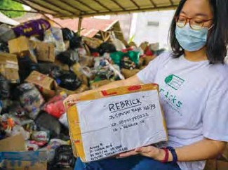 ??  ?? Novita Tan, cofondatrice de Rebrick, à Jakarta, en Indonésie, montre des déchets plastiques réduits en petits morceaux qui seront transformés en briques,