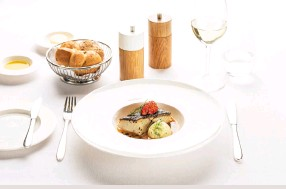 ??  ?? Main course in First Class sautéed black cod fillet with seafood nage