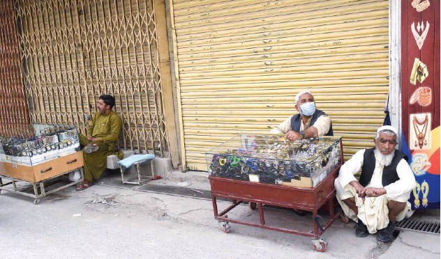?? Agence France-presse ?? ↑ Vendors selling wristwatches sit along a closed market after a lockdown was imposed in Quetta on Saturday.