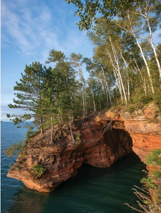 ??  ?? The Apostle Islands are renowned for dramatic red sandstone sea caves dotting the shores (above). John Guillote takes the helm of Bliss, a Jeanneau 349 (opposite top). The author works the windlass in the bow of Bliss (opposite bottom). Shoulder-season cruising means many wide-open anchorages.