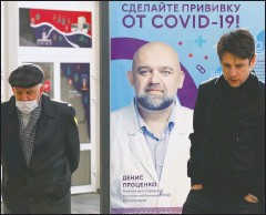 """?? (AP/Alexander Zemlianichenko) ?? Two men stand near a vaccination point decorated with the poster showing a portrait of Dr. Denis Protsenko and words reading """"Get vaccinated against covid-19!!"""" at the Exhibition of Achievements of National Economy in Moscow."""