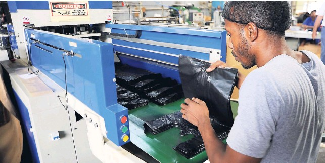 An Unnamed Worker Sorts Plastic Bags Coming Off The Assembly Line At Flexpak During A Tour Of Plant By Members Jamaica Manufacturers Association