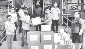 ??  ?? TERIMALAH: Eugene (dua kiri) menyampaikan sumbangan kepada Dr Layang sambil disaksi Calvin (kiri baris dua), Ismawi (tengah) serta yang lain.
