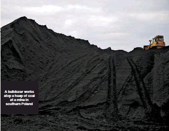 ??  ?? A bulldozer works atop a heap of coal at a mine in southern Poland