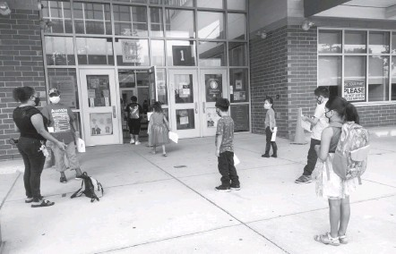 ?? KAYLA RUBLE FOR THE WASHINGTON POST ?? Students attending summer school at a Detroit elementary-middle school in July wait their turn to enter. This year, school districts are exploring classes that go beyond addressing learning loss and remedial work to provide social interactions and emotional support.