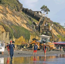 ?? DENIS POROY/ASSOCIATED PRESS ?? Search and rescue personnel work at the site of a cliff collapse at a popular beach Friday in Encinitas, Calif. Three members of a family died when an oceanfront bluff collapsed at Grandview Beach north of San Diego, authorities said.