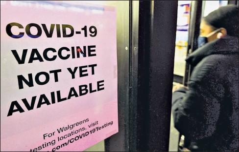 ?? JUSTIN LANE / EFE ?? • Una mujer entra en una farmacia de Nueva York, donde se ve un cartel que dice que la vacuna aún no está disponible.