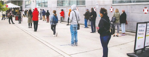 ?? Carlos Osorio / REUTERS ?? People wait in line at the Women's College COVID-19 testing facility in Toronto last month.
