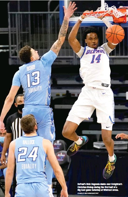 ?? CHARLES REX ARBOGAST/AP ?? DePaul's Nick Ongenda dunks over Creighton's Christian Bishop during the first half of a Big East game Saturday at Wintrust Arena.