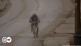 ??  ?? A man rides a bicycle along an ash-covered road near Bridgetown, Barbados. The neighboring island of St. Vincent has seen large clouds of ash after a volcanic eruption