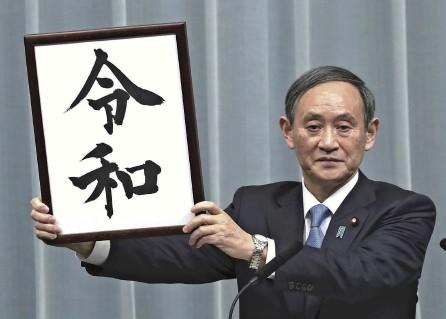 ?? Yomiuri Shimbun file photo ?? Then Chief Cabinet Secretary Yoshihide Suga holds up the calligraphic work used to announce the new Reiwa era name to the public on April 1, 2019.