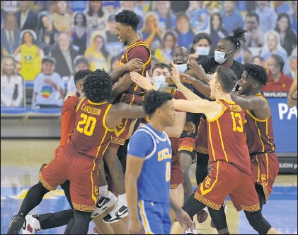 ?? PHOTOS BY MARK J. TERRILL — THE ASSOCIATED PRESS) ?? USC's Tahj Eaddy, top, celebrates with teammates as UCLA's Jaylen Clark exits the court after Eaddy hit a winning 3-point shot with a second left.
