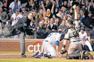 ?? AP ?? Home plate umpire Mike DiMuro calls the Cubs' Nate Schierholtz out at home as Pirates catcher Russell Martin shows DiMuro the ball.