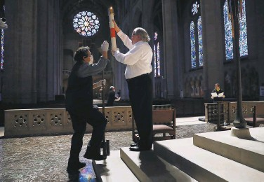 ?? Scott Straz­zante / The Chron­i­cle ?? John Hor­ton (left) and Charles Ship­ley put a can­dle in place be­fore a vir­tual ser­vice on Easter Sun­day at Grace Cathe­dral in San Fran­cisco. Church lead­ers are crit­i­ciz­ing city restrictio­ns on in­per­son ser­vices.