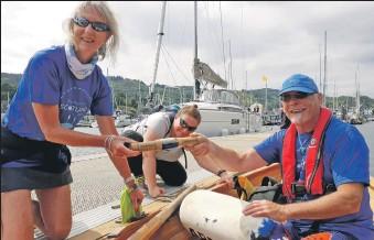 ??  ?? The Row Around Scotland baton is handed over in Tarbert Harbour.